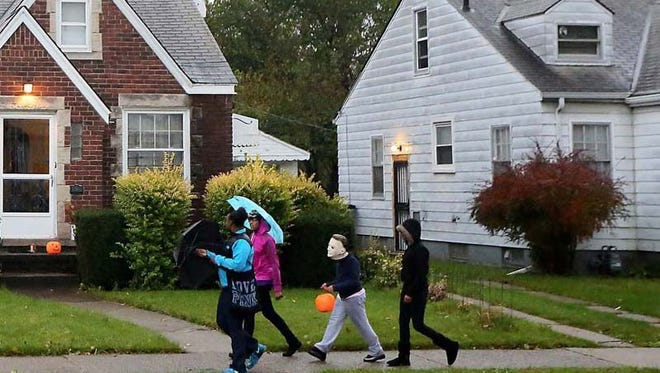 Trick-or-treaters walk down Alma St.. in Detroit on Thursday, Oct. 31, 2013.