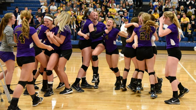 Members of the Lexington volleyball team celebrate after beating Ottawa-Glandorf 3-1 Saturday in Ontario to win the Division II regional championship at Ontario.