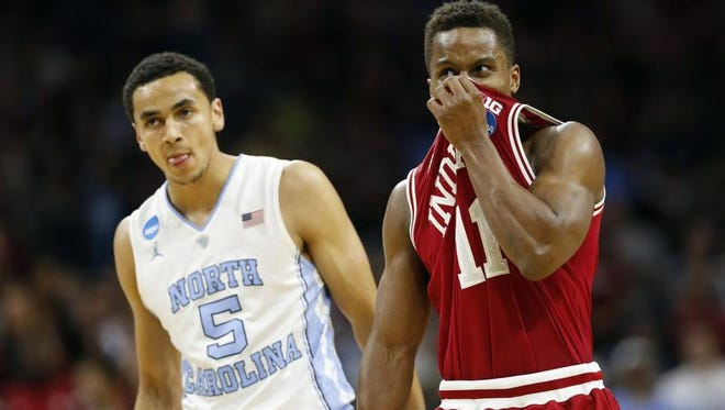 Indiana's Yogi Ferrell, right, wipes his face as he passes North Carolina's Marcus Paige during the second half of an NCAA college basketball game in the regional semifinals of the men's NCAA Tournament, Friday, March 25, 2016, in Philadelphia. (AP Photo/Chris Szagola)