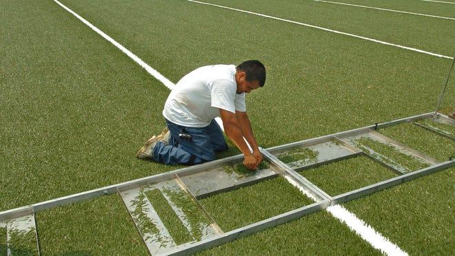 Martin Martinez cuts hash marks in the Sprinturf field being installed in Newport High School's football stadium in 2006.