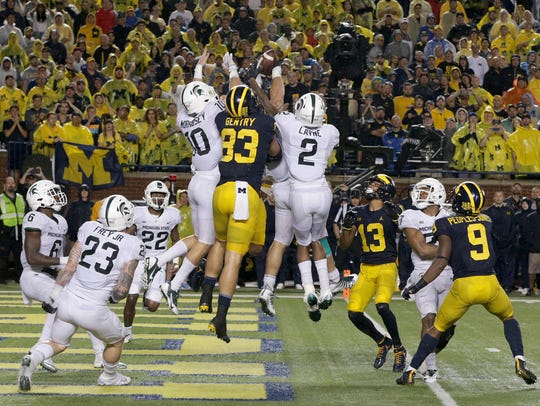 Michigan and Michigan State players contest a Hail