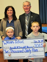 """Wilson School 1st grade teacher Marie Morris and 1st graders Maria Shirk and Hudson Factor join James Malloy of the Ronald McDonald House as he accepts a generous donation raised during the school's """"Month of Hope"""" in January."""