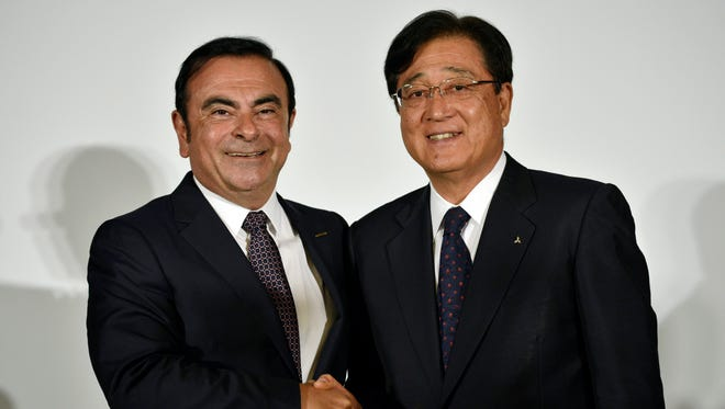 Nissan Motor Co.'s Chairman and CEO Carlos Ghosn (L) shakes hands with Mitsubishi Motors Corp.'s Chairman and CEO Osamu Masuko during a joint press conference in Yokohama, near Tokyo, Japan on May 12, 2016.