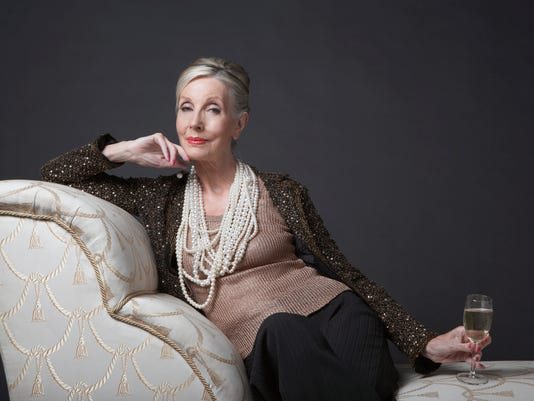 Elegant Senior Woman On Chaise Lounge With Champagne