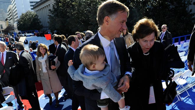 Gov. Bill Haslam escorts his mother-in-law, Chris Garrett, up the podium as he holds his grandson Will Colquitt after his inaugural ceremony at Legislative Plaza on Saturday.