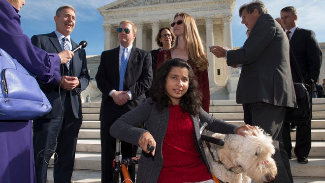 Ehlena Fry, 12, sits with her service dog Wonder Monday after the Supreme Court her her Americans with Disabilities Act case.