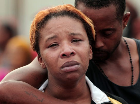 Lesley McSpadden is comforted by her husband, Louis