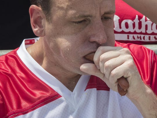 Reigning champion Joey Chestnut eats two hot dogs at a time during the men's competition of the Nathan's Famous Fourth of July hot dog eating contest, Wednesday, July 4, 2018, in New York's Coney Island. The defending champion broke his own world record by eating 74 hot dogs in 10 minutes. (AP Photo/Mary Altaffer)