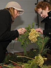 Sara Buss and her mother, Judy Buss, assemble a festive wreath during a Natural Christmas at The Ridges Sanctuary.