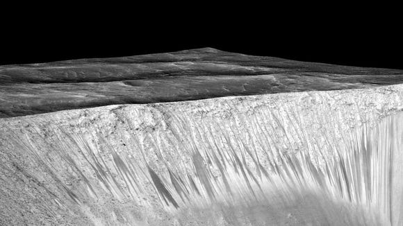A handout image released by NASA on Sept. 28, 2015, shows dark narrow streaks  that are hypothesized to be formed by the flow of briny liquid water on Mars.