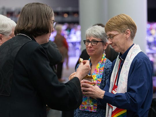 Bishop Elaine Stanovsky (left foreground) receives Holy Communion from Sue Laurie (right) and Julie Bruno  during opening worship at the 2016 United Methodist General Conference in Portland, Ore. Laurie and Bruno, prominent activists for greater inclusion of gays and lesbians in the life of The United Methodist Church, were married outside the 2008 General Conference in Fort Worth, Texas.