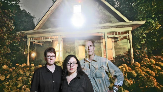 Wendi Garringer (left) and Pepper Partin stand in front of their Irvington home with Indianapolis Star reporter Will Higgins, who through Michelle Pemberton's photographic tricks is made to look ghostly.