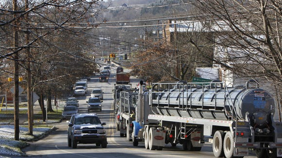 In this 2011 file photo, a long line of giant water tanker trucks rumble into the heart of Mansfield, Pennsylvania, on their way to natural gas drilling operations.