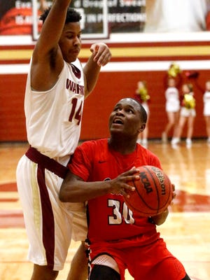 Oakland's Timmy Goodrich (30) takes it to the basket while Riverdale's Deron Perry defends Tuesday.