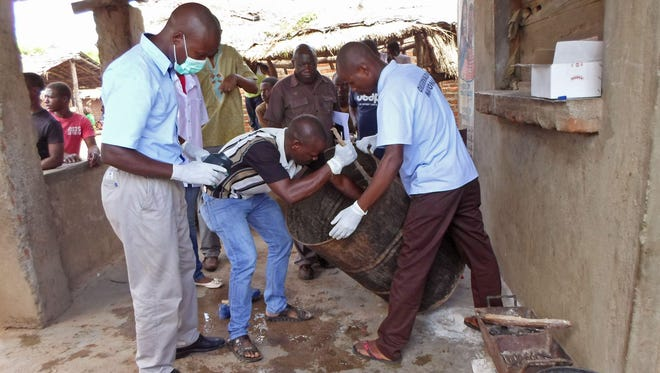 Mozambique government officials gather samples from a drum that was used to brew traditional local beer that killed dozens of people in Tete, Mozambique. According to the Associated Press, police say the drum has since disappeared, complicating the investigation.