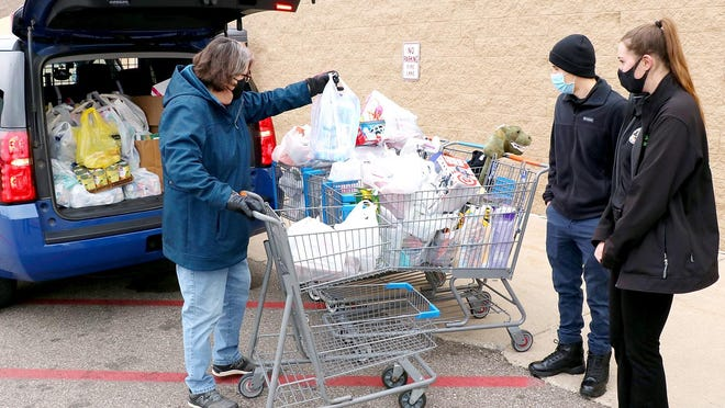 """A donor places purchased items into one of the collection carts Saturday at Walmart in Sturgis, for """"Stuff a Blue Goose."""""""