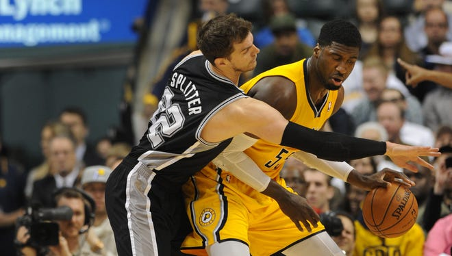Indiana's Roy Hibbert tries to keep the ball away from San Antonio's Tiago Splitter in the second quarter  as the Indian Pacers hosted the San Antonio Spurs at Bankers Life Fieldhouse Monday March 31, 2014.