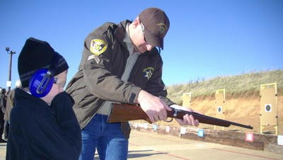 A Caddo Parish Sheriff's deputy helps a youngster operate his grandfather's gun.
