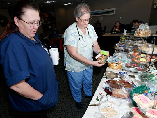 Jenny Rafferty, left, scans the dessert table while Debbie Hobczuk examines a jar of granola Tuesday at the Holiday Extravaganza at Arnot Ogden Medical Center in Elmira.