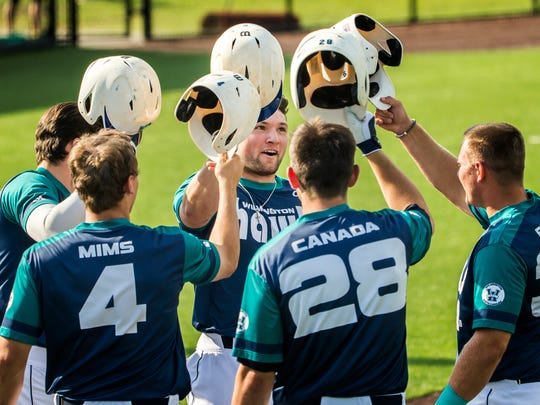 UNCW players congratulate teammate Casey Golden (center) after his grand slam in Delaware's 12-2 loss to UNCW at Hannah Stadium at the University of Delaware on Thursday afternoon.