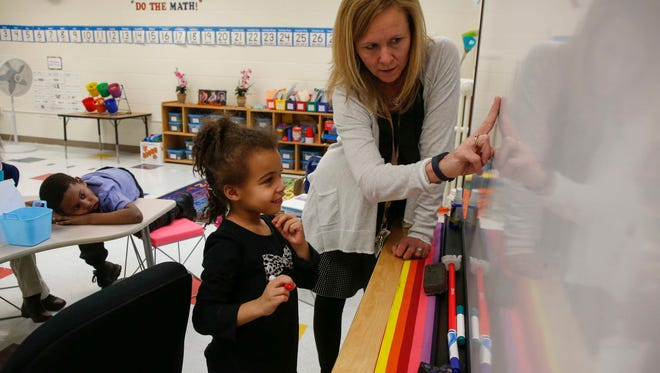 Aaliyah Hunley, 6, works on a project with Theresa Merhl, a teacher at Moulton Elementary School in Des Moines on Thursday, March 3, 2016. An interventionist at Moulton, Merhl works in different classrooms with struggling students in small groups.