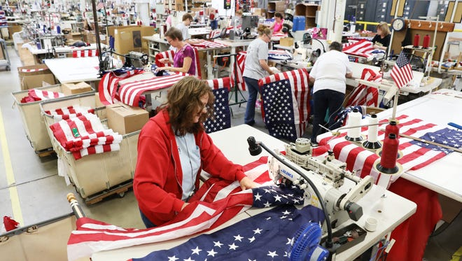 """Anita Arnold does the """"long sew"""" at Annin Flag Company in Coshocton. Each of the company's sewn flags starts as individual strips of color and a field of stars. The field of stars is sewn to a short length of seven stripes to form the top portion of the flag, which is then sewn to a longer section of six stripes."""