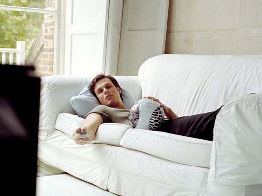Man lying on sofa using television remote control