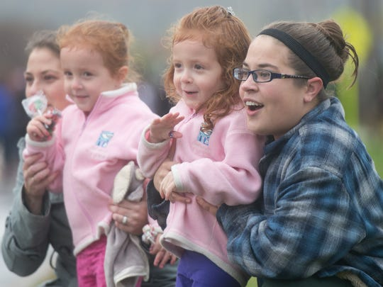 Amber Conway (from left) and her 3-year-old twins Felicity and Eloise along with Saige DeCleene watch the De Pere High School's OctoBIRD Fest parade go by their neighborhood Friday in De Pere.