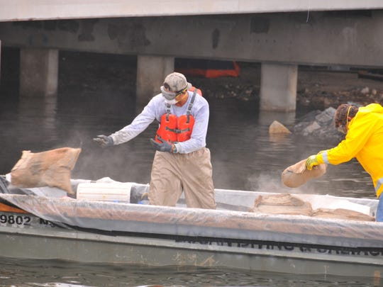 Workers throw bags of concrete to a diver in a dive suit working under water. Crews from Logan Diving and Salvage work to shore up a damaged pipe that runs under the Indian River parallel to State Road 520. The workers were placing porous concrete bags to shore up the pipe that was undermined in and pulled apart in Hurricane Irma. The pipe caries drinking water to the barrier islands.