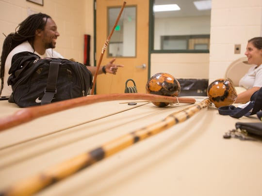 A berimbau is a musical instrument integral to capoeira. Music is important in the Brazilian martial art form. Instructor James Green III and student Cassandra Biscardi practice singing before the class's martial art segment.