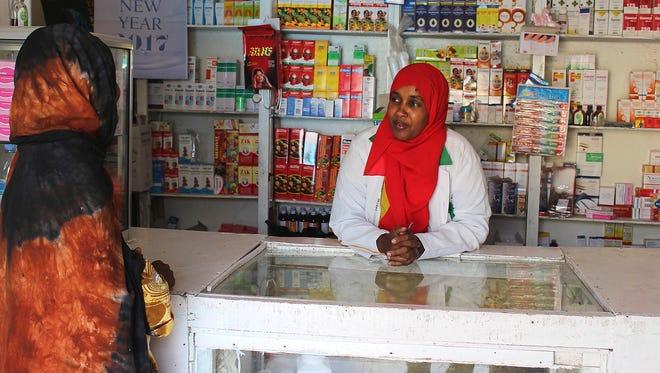Sahra Mohamed Ali talks to a customer in the pharmacy that she runs in Hargeisa, Somalia.