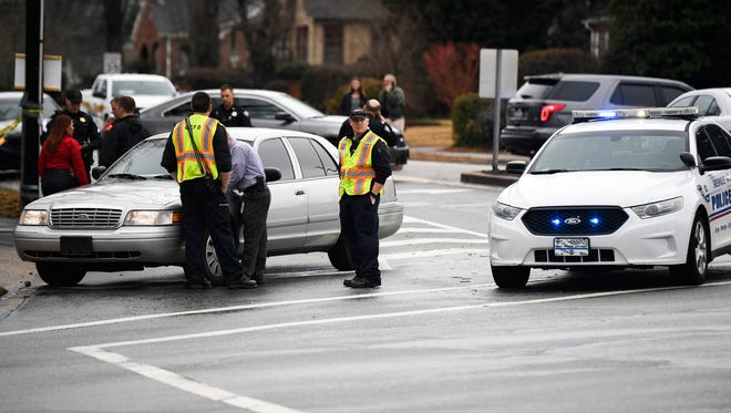 Greenville Police Department officers investigate the site of a shooting on the corner of North Main Street and Rutherford Road on Wednesday, Feb. 7, 2018.