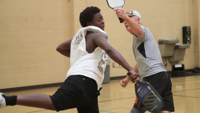 Tirrell Johnson, left, and teammate John Montero return a ball in their pickleball game at the James O. Jessie Center in Palm Springs, Calif., June 25, 2018.
