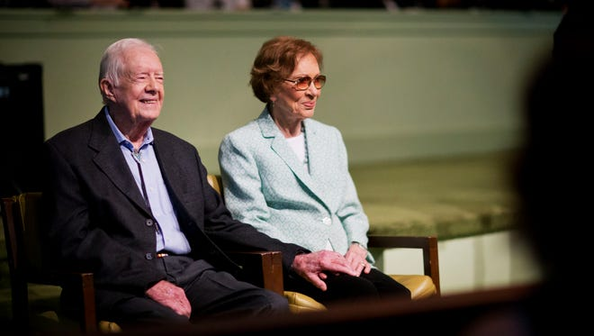 Former President Jimmy Carter (left) sits with his wife, Rosalynn, as they wait to pose for photos after Carter taught Sunday School class Sunday, Aug. 23, 2015, at Maranatha Baptist Church in his hometown of Plains, Ga.