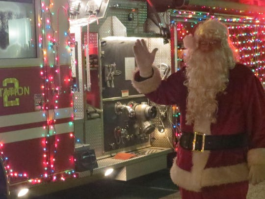 Santa Claus gets ready to board a firetruck for his ride through downtown Hammonton.