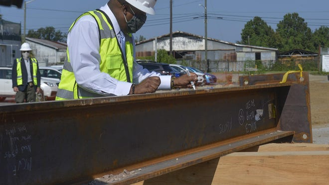 Mayor Van Johnson signs his name on an I-beam at the arena worksite.