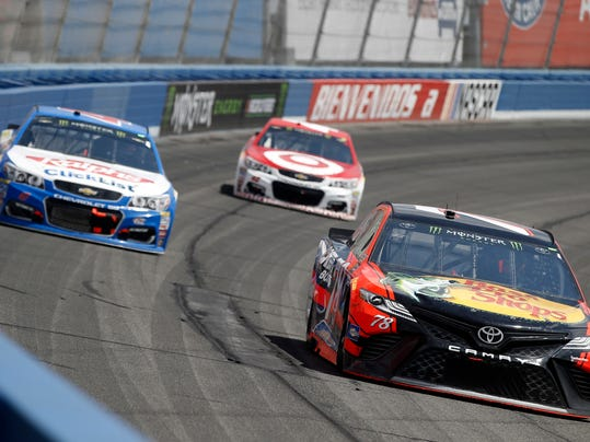Martin Truex Jr., right, takes the lead, in front of AJ Allmendinger, left, and Kyle Larson, center, in the NASCAR Cup Series auto race at Auto Club Speedway in Fontana, Calif., Sunday, March 26, 2017. (AP Photo/Alex Gallardo)