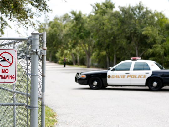 Police block the entrance to Silver Lakes Rotary Nature Park on Friday, June 8, 2018, in Davie, Fla. Someone called police after seeing a woman who was walking her dog in the park being dragged into a lake by an alligator.
