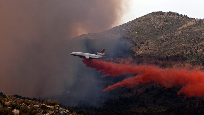 Tanker 910 makes a retardant drop on the Yarnell Hill Fire to help protect the Double Bar A Ranch near Peeples (cq) Valley, Arizona 06/30/13. The lightning caused blaze began on Yarnell Hill Sunday, June 30, 2013. (Photo by Tom Story)