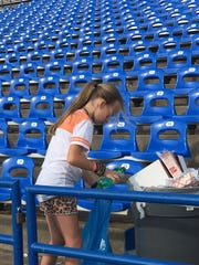 Molly Moore, 10, picks up plastic bottles at San Angelo Stadium after a football game, as part of the Game Recyclers' effort to collect all the recyclables that were being left on the ground.