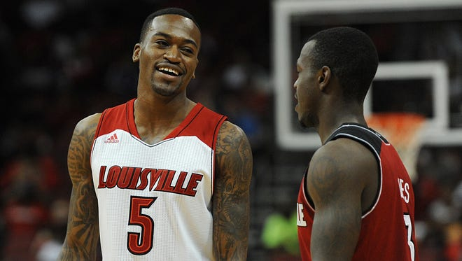 Kevin Ware (5) didn't play during the Red-White Scrimmage game but shared a light moment with Chris Jones (right) at the KFC Yum! Center on Saturday. Oct. 12, 2013
