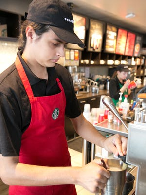 Adam Mitchell, 25, foreground, and Sierra Anaya, 20, work at the Starbucks on East University Avenue on Christmas. The store had steady business, serving as many as 200 customers before noon, said shift manager Jesus Salazar.