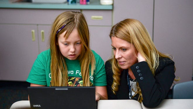 Heather Crosser, right, helps Charlize Brostron learn coding skills with her fourth grade class at Johnson Elementary Thursday, Dec. 11, 2014, in Fort Collins, CO. The coding class, run through Code.org, is being used nationwide to teach students computer science.