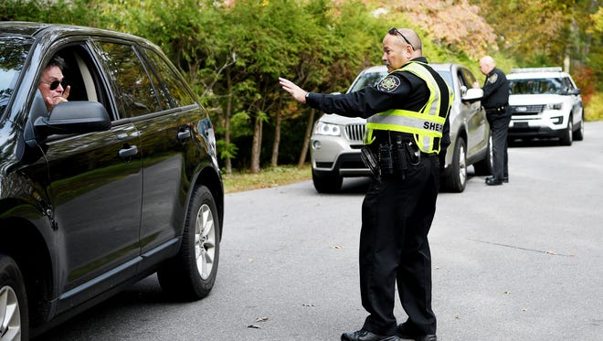 Buncombe County Sheriff's Corporal Jackie Burnette, foreground, and Deputy Chief Terry Rogers check cars on Browntown Road in Biltmore Forest November 1, 2017.