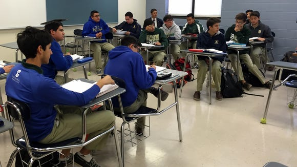 Cathedral High School students listen to a teacher in class.
