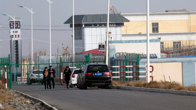 In this 2018 file photo, people walk by a police station by the front gate of the Artux City Vocational Skills Education Training Service Center in Artux in western China's Xinjiang region. A coalition of human-rights groups has met with the International Olympic Committee over calls to pull the 2022 Winter Olympics out of Beijing.