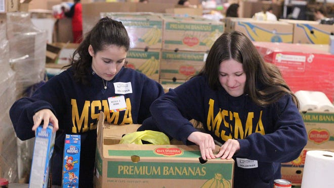 Seniors Nicole Marie Zastko and Madelynn C. Wellons organize and package food donations at the Community Food Bank in Hillside as part of Mount Saint Mary Academy's Service Day, which was held on March 9.