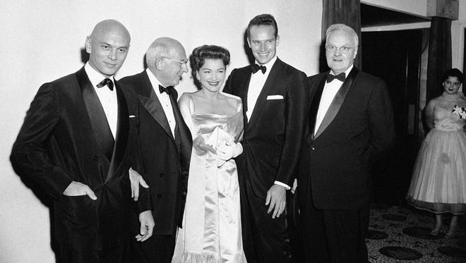 """The actors and producer of """"The Ten Commandments"""" pose for pictures in the lobby of a Los Angeles theater on Nov. 14, 1956. Left to right: Yul Brynner, who played the role of Pharaoh Ramses II, Cecil B. De Mille, who produced the picture; Anne Baxter, who played Queen Nefertiti; Charlton Heston, who played Moses; and Dr. William Lindsey Young, western vice president of the National Conference of Christians and Jews. The Ten Commandments will be shown on ABC at 7 p.m. on April 15."""