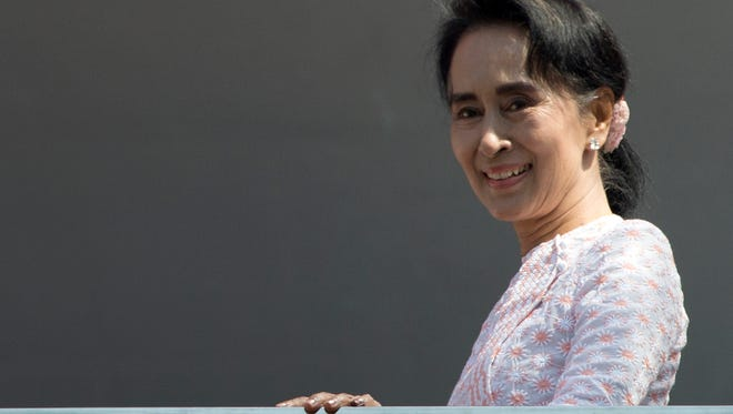 Aung San Suu Kyi, leader of Myanmar's National League for Democracy party, smiles to her supporters after delivering a speech from a balcony of her party headquarters in Yangon, Myanmar. Myanmar's election panel has released results showing that Aung San Suu Kyi's opposition party has secured a historic majority in Myanmar's Parliament.