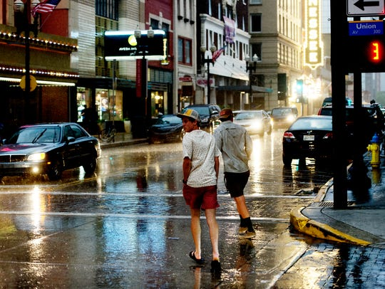 People cross Union and Gay Street during a rain shower